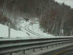 A car coming down the on ramp from the northbound Old Man of the Mountain Viewing Area.